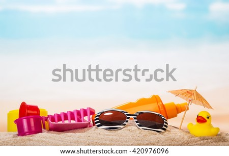 Children's toys, sunglasses and cream in the sand against the sea. - stock photo