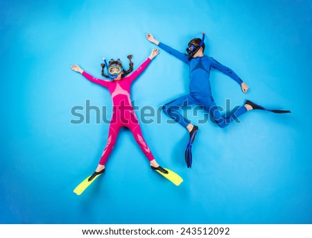 Children scuba diving deep in the sea. Studio shot on a blue background. - stock photo