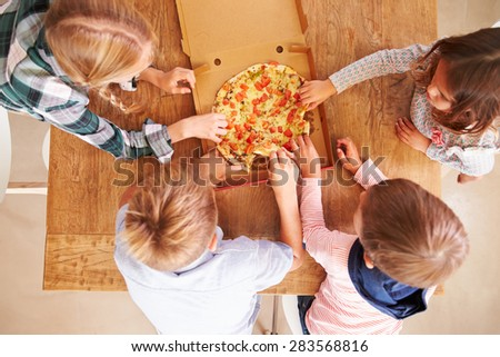 Children sharing a pizza together, overhead view - stock photo
