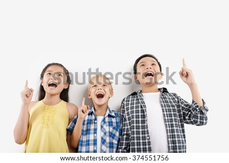 Children shouting and pointing up, isolated on white - stock photo
