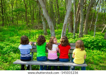 Children sister and friend girls sitting on park bench looking at forest and smiling - stock photo