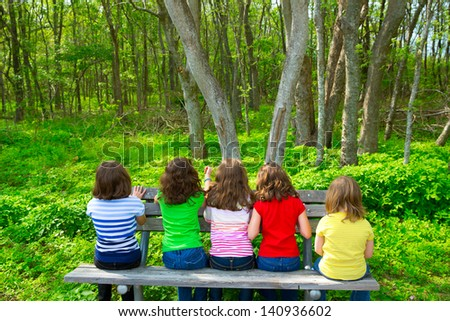 Children sister and friend girls sitting on park bench looking at forest rear view - stock photo