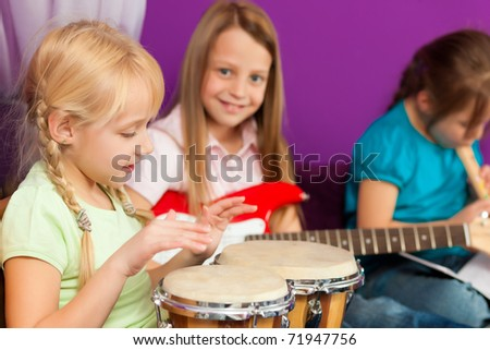 Children � sisters - making music; they are practicing playing guitar, bongo and flute - stock photo