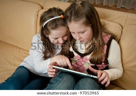 Children (sisters) playing with tablet at home on sofa - stock photo