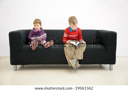 Children sit on couch and read