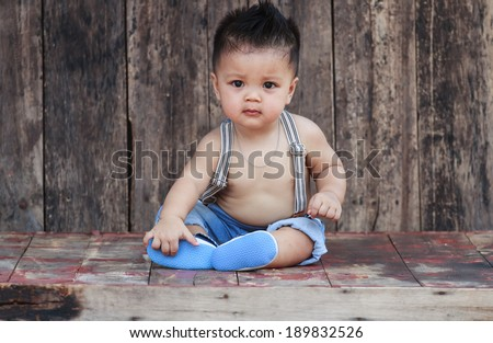 Children sit on the wooden floor and wooden walls.