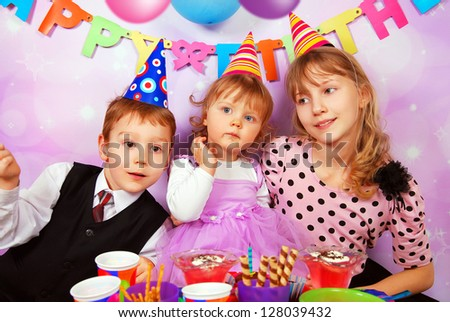 children sitting at the table and celebrating first birthday of baby girl