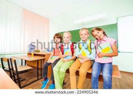 Children sitting in row on desk with textbooks