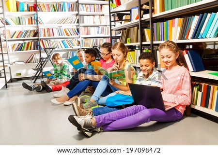 Children sitting on floor in library and studying - stock photo