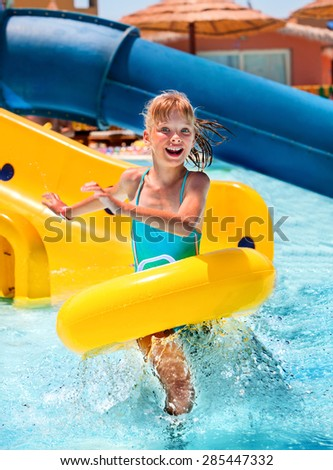 Children sitting on yellow inflatable ring in swimming pool. - stock photo