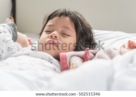 Children sleeping on a white bed with happiness.