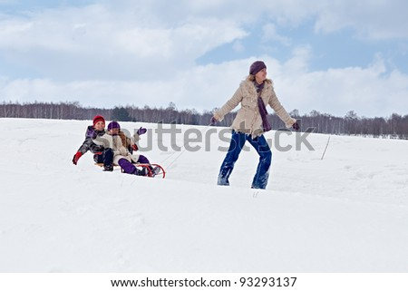 Children sleigh riding - their mother pulling in winter landscape
