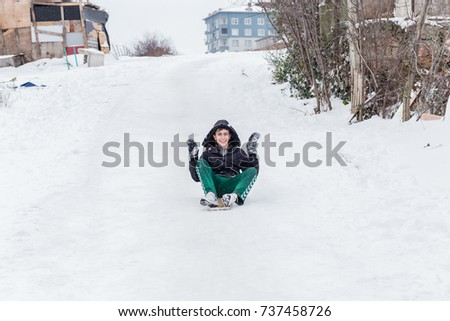 Children slide on snow in old school style with hardwood sled in Istanbul.Happiness and joy concept.Istanbul,Turkey.31 December,2015