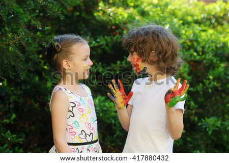 Children soiled with paint, having fun and looking at each other. Child has fun painting / drawing. Children's creativity. Art for baby. Emotions. Children playing.  - stock photo