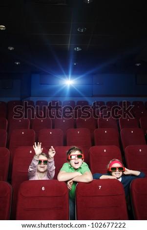 Children spending time with pleasure in the movie theatre - stock photo