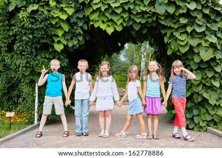 Children stand holding hands with their backs to tunnel made from green plants and leaves - stock photo