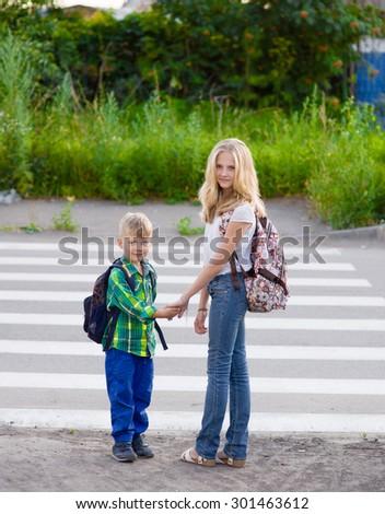 Children stand near a pedestrian crossing - stock photo