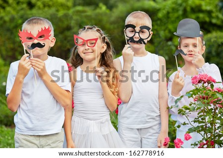 Children stand together in summer park holding masks on stiks at their faces - stock photo