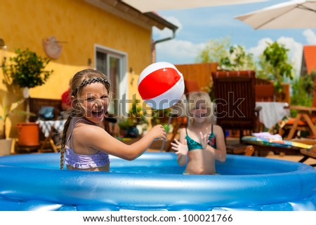 Children - they are sisters - playing in water with a ball in the garden in front of the house - stock photo