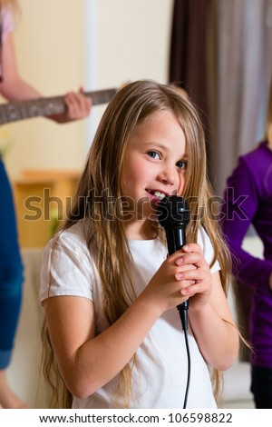 Children - three sisters - playing in a band making music, focus on girl with microphone in front - stock photo