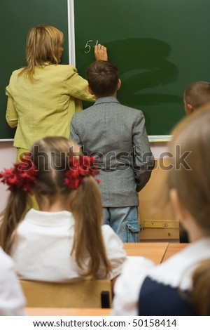 Children together with the teacher in a classroom at a mathematics - stock photo