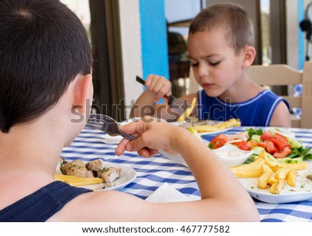 Children, two boys, eating fish, chips and salad at the table at home or in restaurant.