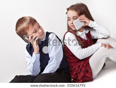 Children use their mobile phones and look at each other, on a white background - stock photo