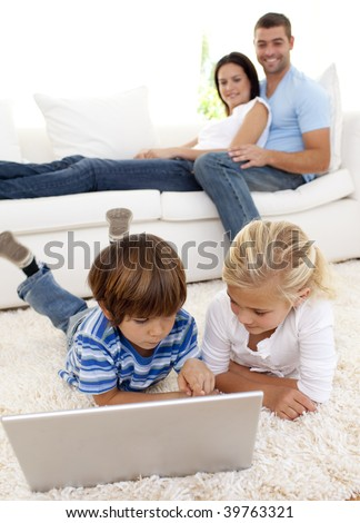 Children using a laptop on floor and parents lying on sofa