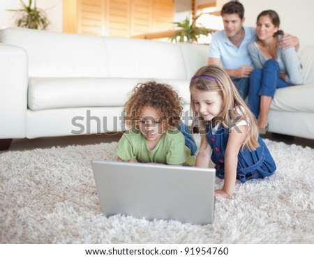 Children using a notebook while their parents are watching in their living room - stock photo