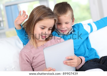 Children using electronic tablet at home - stock photo