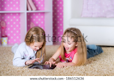 children using modern tablet PC laying on the floor in the polka-dot bright pink room at home fun game together - stock photo