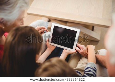 Children using tablet with their grandparents at home - stock photo