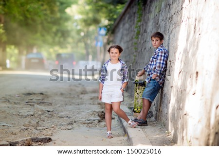 Children walk in the park. Brother and sister walking on the street. Beautiful fashionable children.