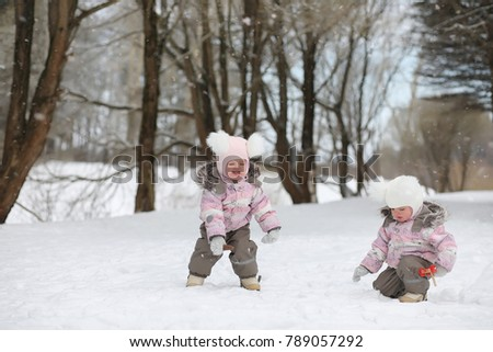 Children walk in the park in winter. Winter forest family with children on a walk. A cold winter day is a family walk.
