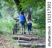 Children walking  in forest.  Llittle boy walking with his bike high up - stock photo
