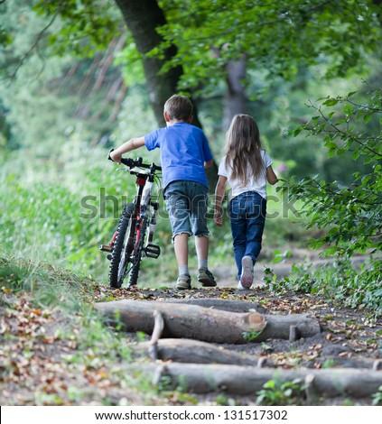 Children walking  in forest.  Llittle boy walking with his bike high up - stock photo