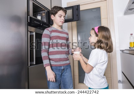 Children warming a glass of milk in the microwave - stock photo