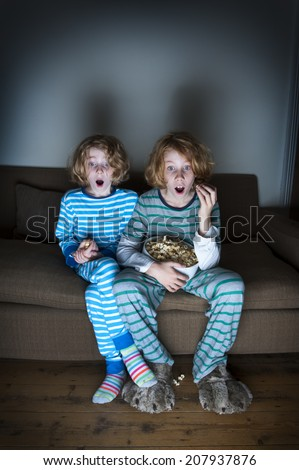 children watching tv shocked and surprised - stock photo