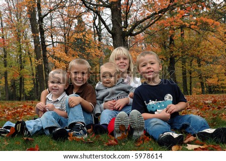 children with autumn trees in the background - stock photo