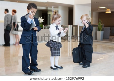 Children with communication devices in the business clothing in the business center with with adults in the background - stock photo