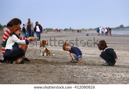 Children with dog on the beach in Lido , Venice Italy , September 26, 2015 - stock photo
