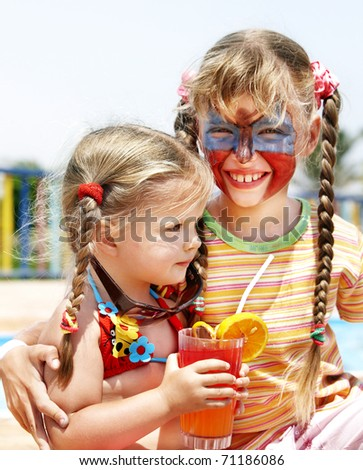 Children with face painting drinking orange juice.