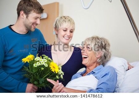 Children with flower bouquet visiting happy mother in hospital - stock photo