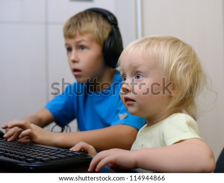 children with headphones looking at the monitor - stock photo
