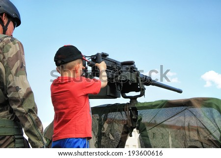 children with machine gun during a military show in Laudun, France