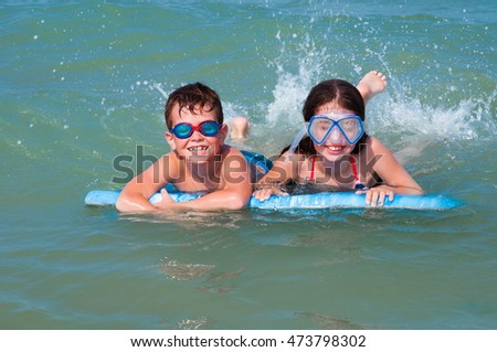 Children with mask and glasses swimming with a surf board