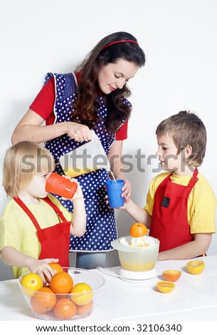 Children with mother drinking orange juice - stock photo