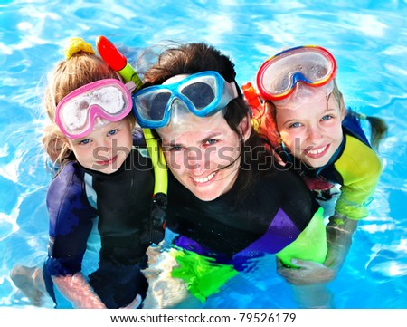 Children with mother  in swimming pool learning snorkeling.