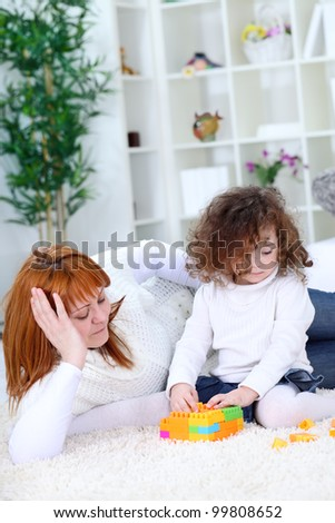 children with mother playing on floor in living room