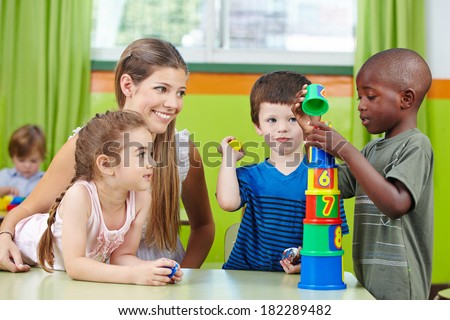 Children with nursery teacher building tower in a kindergarten group - stock photo